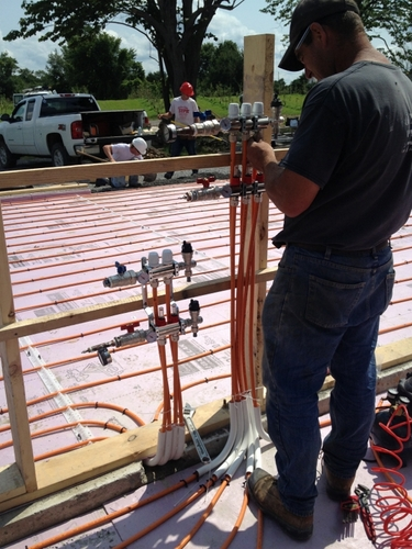 A worker installs a manifold system for plumbing on a new construction